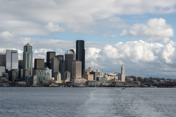 City At Waterfront Against Cloudy Sky