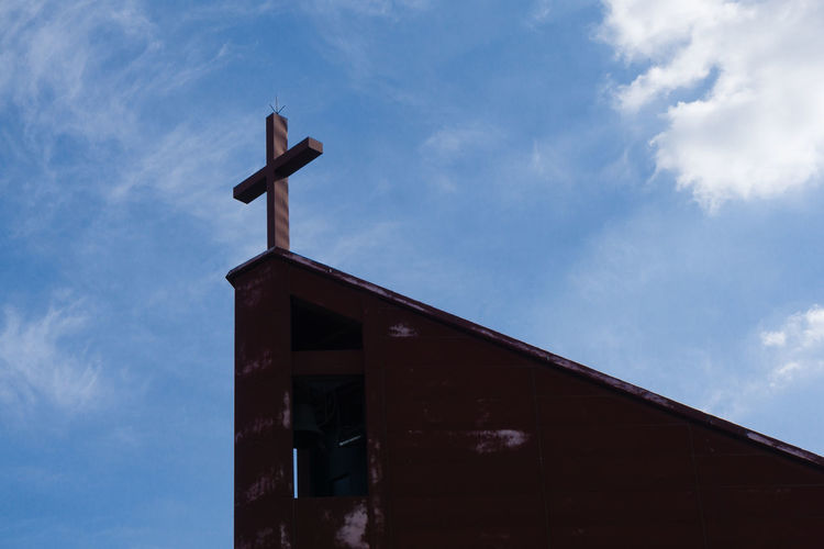 Low angle view of cross on building against sky