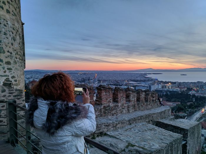 Rear view of woman photographing cityscape at sunset