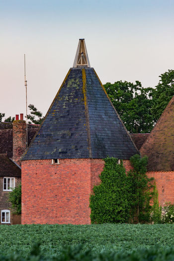Oast house,Garden of England, Kent, England. Architecture Built Structure Building Exterior Plant Sky Building Nature Tree No People Clear Sky Day House Outdoors Travel Destinations Sunlight Roof The Past Triangle Shape History Shape Hedge Oast House Hops Tourism Getty Images Vivid International Rural Scene Village Tranquil Scene Wheat Field Church Tower
