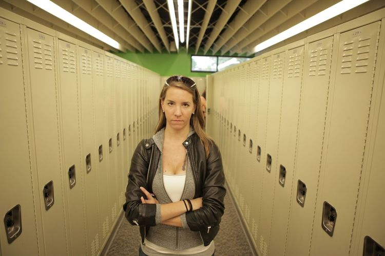 Portrait Of Serious Young Woman With Arms Crossed Standing In Locker Room