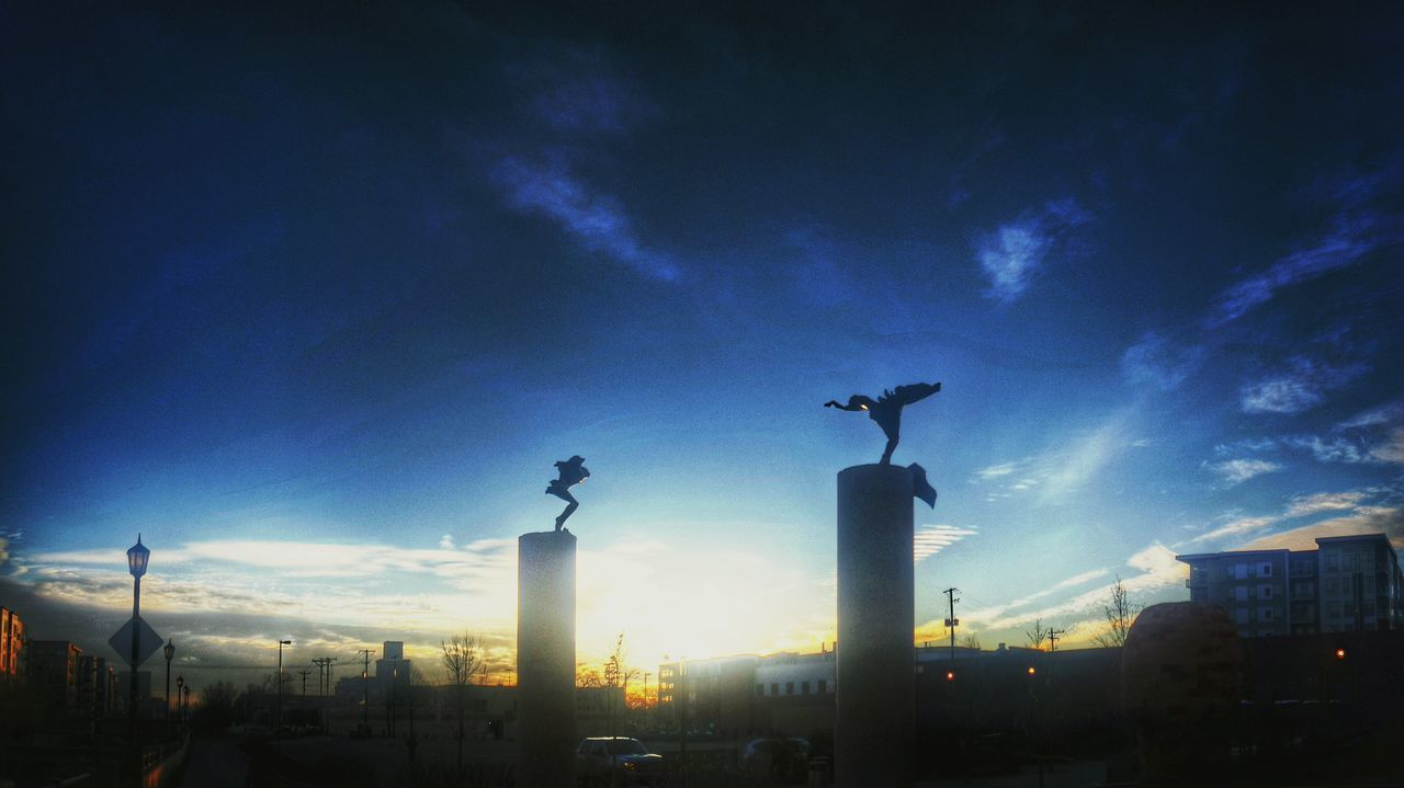 animal themes, bird, sky, one animal, architecture, statue, animals in the wild, sculpture, city, building exterior, built structure, low angle view, cloud - sky, outdoors, no people, sunset, perching, cityscape, spread wings, modern, day, nature