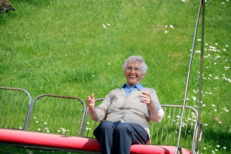 Portrait of smiling senior woman sitting on swing at park