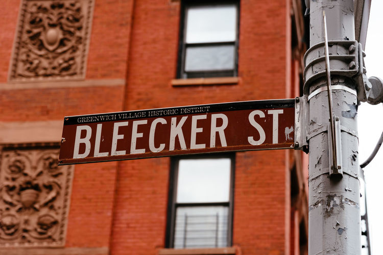 Street name sign in Greenwich VIllage Bleecker Street Manhattan USA West Village Architecture Brick Brick Wall Building Building Exterior Built Structure City Communication Day Greenwich Village Guidance Information Low Angle View Manhattan Bridge No People Outdoors Red Sign Street Street Name Sign Text Wall Wall - Building Feature West Side Western Script Window