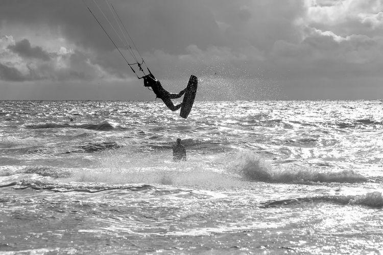Silhouette kite surfing in the ocean