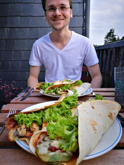 Smiling Young Man With Food In Restaurant