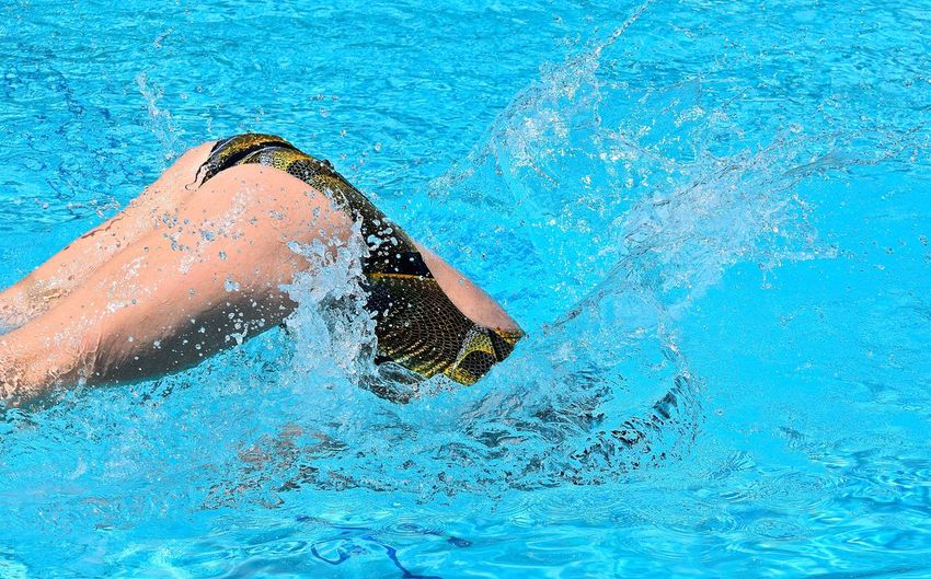 Midsection of woman swimming in pool