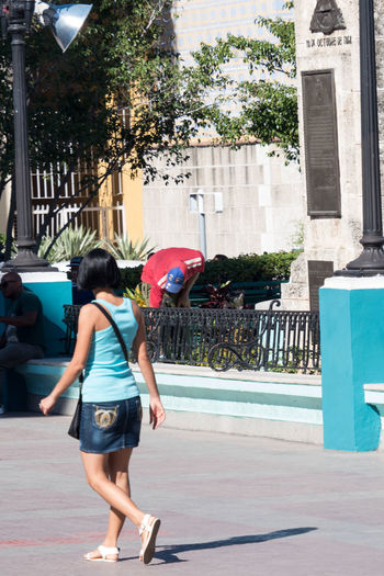Asian tourist girl adapts to dominating colors in Cuba Adult Adults Only Architecture Built Structure City Day Full Length Long Hair One Person One Woman Only One Young Woman Only Only Women Outdoors People Plaza De Cespedes Rear View Sky Street Tree Women Young Adult Young Women