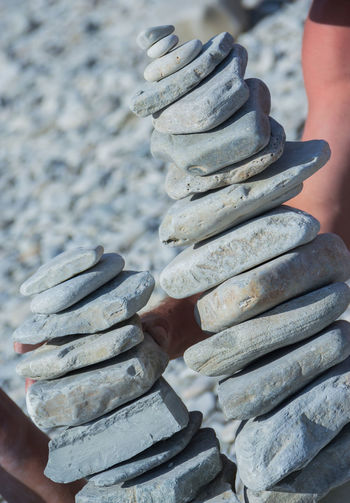 the towers of pebble stones on the beach, games on the beach Human Hand Hand Stack One Person Real People Focus On Foreground Holding Human Body Part Day Metal Close-up Balance Unrecognizable Person Outdoors Lifestyles Solid Nature Body Part Leisure Activity Finger