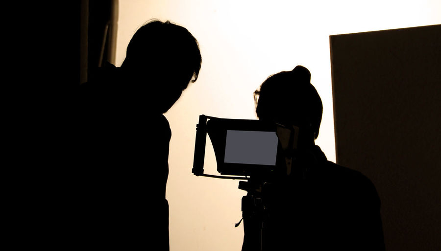 Shooting studio behind the scenes in silhouette images which film crew team working for filming movie or video with professional lighting and equipment such as camera, tripod, soft box, monitor Technology Silhouette Indoors  Photography Themes Two People Real People Men Women Adult Photographic Equipment People Lifestyles Photographing Camera - Photographic Equipment Standing Camera Screen Leisure Activity Holding Occupation Digital Camera Photographer Behind The Scenes Filming Studio; Photo; Shoot; Photography; Photographer; Equipment; Film; Model; Fashion; Professional; Behind; Shooting; Background; Camera; Photoshoot; People; Tv; Production; Lighting; Product; Scenes; Set; Woman; Light; Video; Black; Movie; Photograph; Scene;