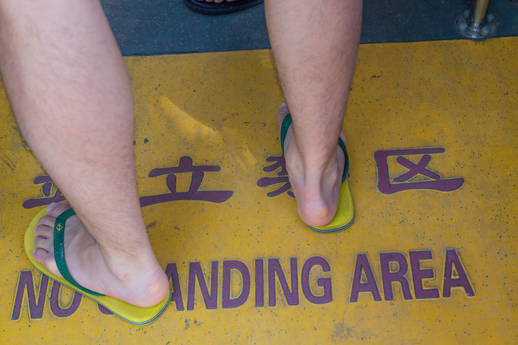Funny Bus Entranc Close-up Cuba Bus English Inscription Chinese Character Forbidden City Forfidden Are Half Light Information Inscription Man's Legs Part Of Sandals Unrecognizable Person Writing Yellow