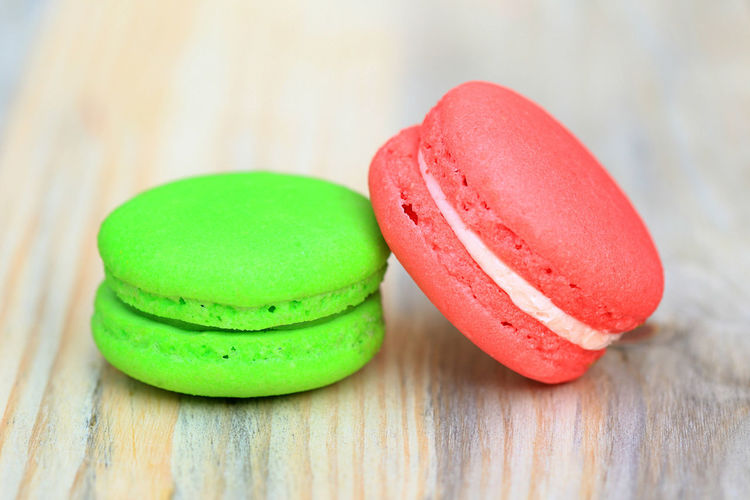 Green and red macaroons on wooden table Close-up Day Filling Up The Tank Flavours Focus On Foreground Food Food And Drink Food Photography Freshness Green Color Indoors  Macaroon No People Outdoors Ready-to-eat Red Round Shape Snack Sweet Food Table Unhealthy Eating Wood - Material