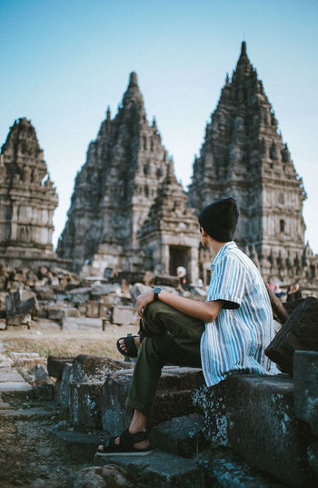 Man Sitting Against Old Temple