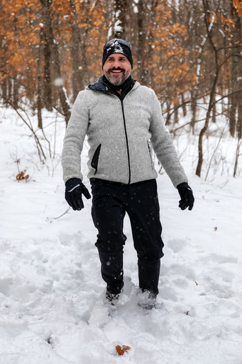Portrait of man standing on snow covered field