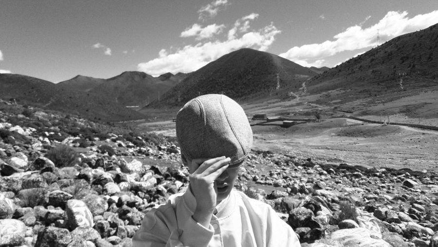 Man wearing flat cap against mountains