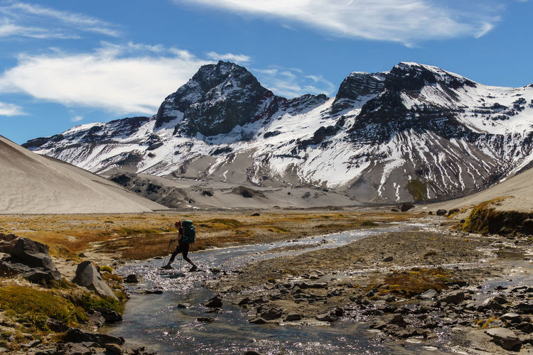Woman crossing stream against snowcapped mountains