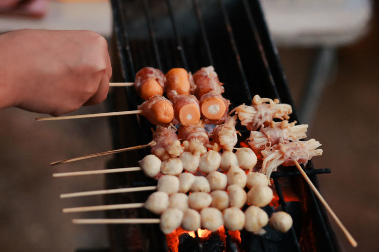 Hand holding meat on barbecue grill