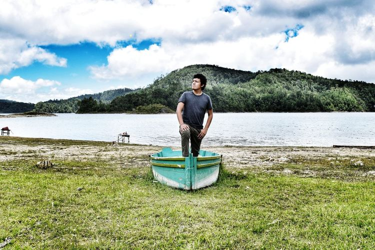 Man standing in boat moored on field by lake against sky