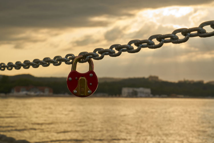 Close-Up Of Lock Attached To Chain Against Sea At Sunset