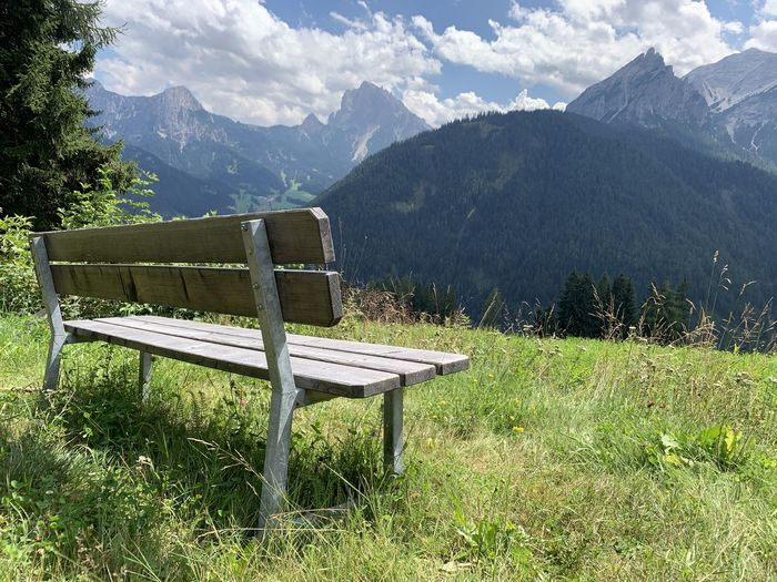 Empty bench on field against mountains
