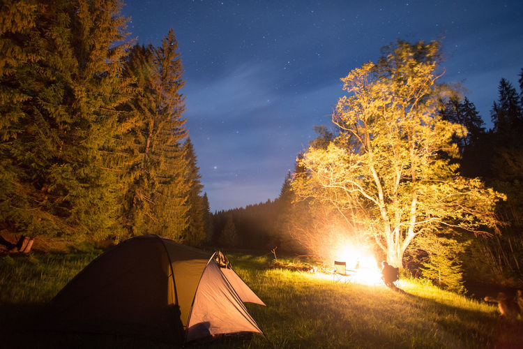 Person sitting by bonfire while camping in forest at night