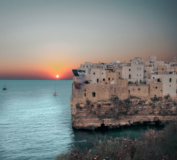 Scenic view of sea against buildings during sunset