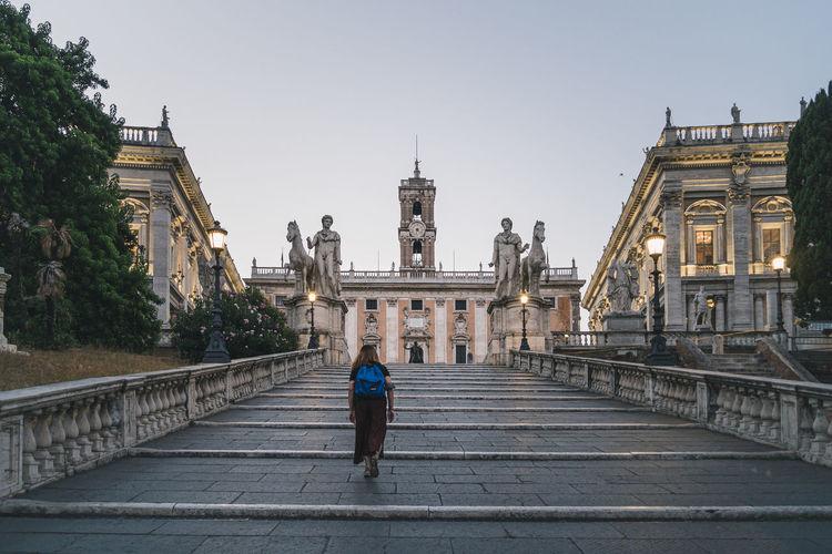 People walking in temple against sky in city
