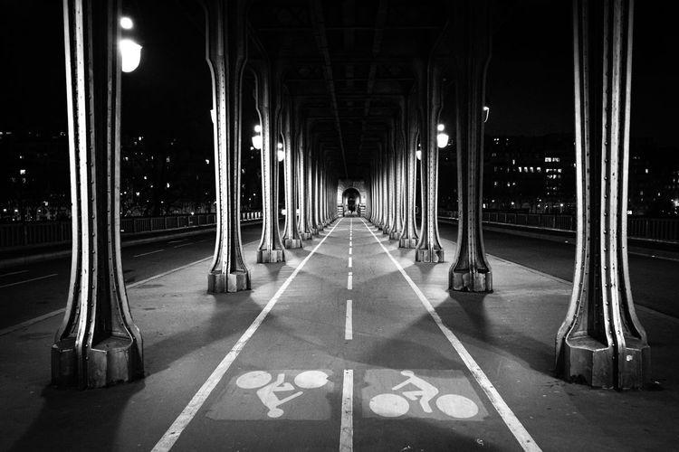 Empty road along illuminated lights at night
