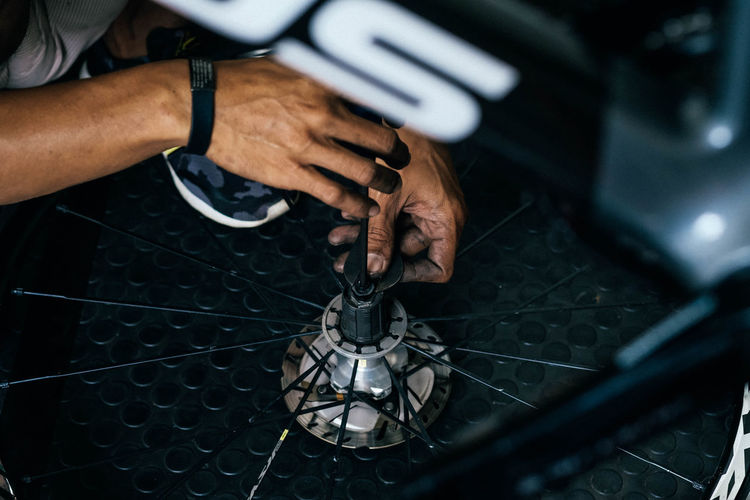 Cropped image of man repairing bicycle wheel