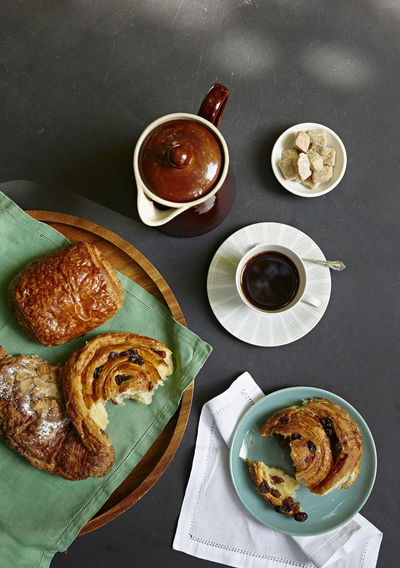 Overhead shot of a breakfast of pastries and coffee on a a slate table top. Appetizer Bowl Breakfast Brew Coffee Directly Above Food Food And Drink Food State Food Styling Freshly Baked Freshness High Angle View Homemade Indulgence Meal Morning Outside Pastries Plate Ready-to-eat Serving Size Still Life Table Temptation