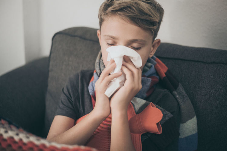 Boy suffering from cold while sitting on sofa