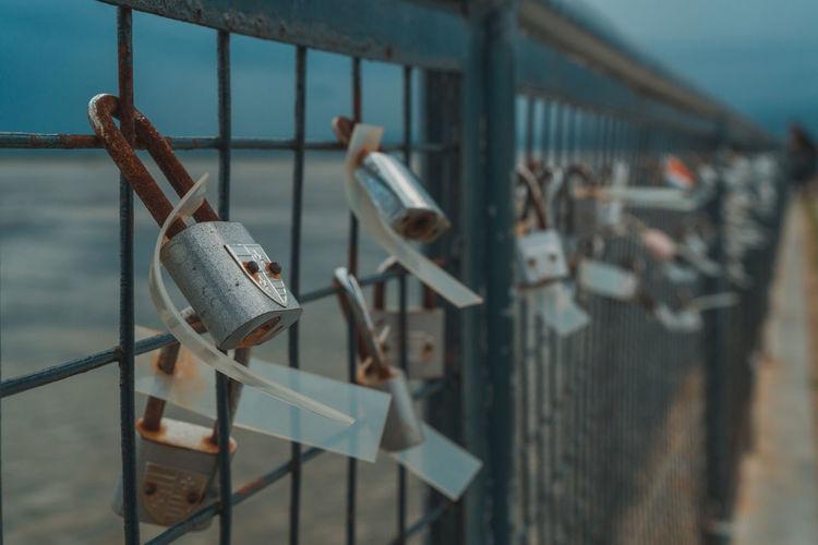 Padlocks hanging on railing by bridge