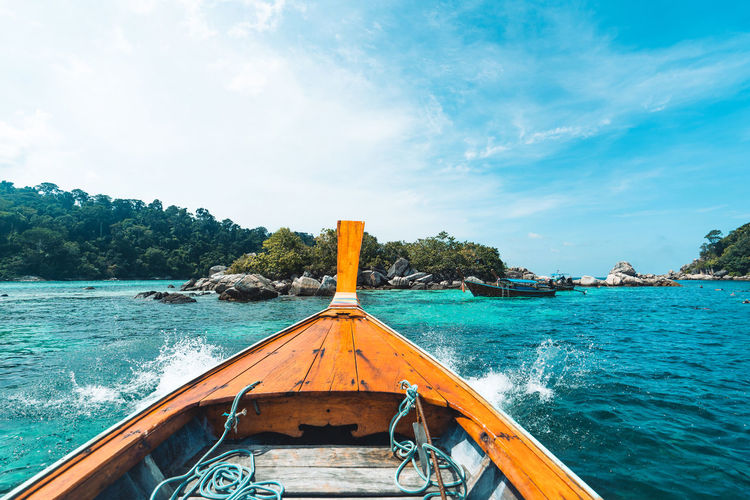 Scenic view of wooden longtail boat sailing in sea against sky