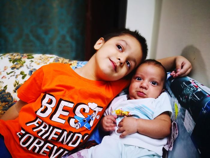 Boy with brother on bed at home