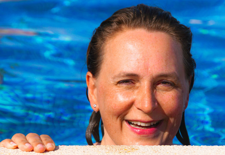 Portrait of smiling woman against swimming pool on sunny day