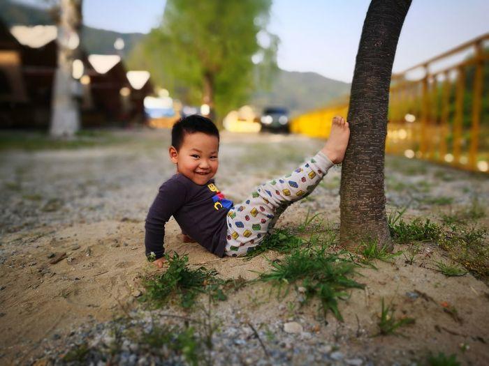 Portrait of cute boy reclining by tree trunk