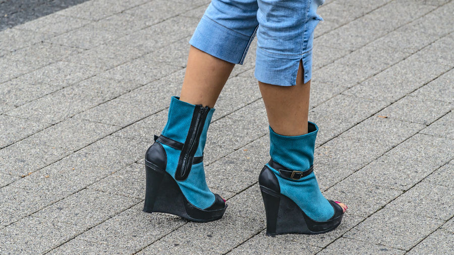 Low section of woman wearing heels standing on footpath