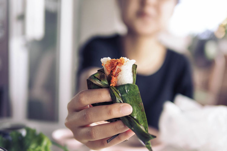 Thai grill sticky rice wrapped by banana leaf Holding Food And Drink Focus On Foreground Food Leisure Activity Close-up Human Hand Day Front View Human Body Part