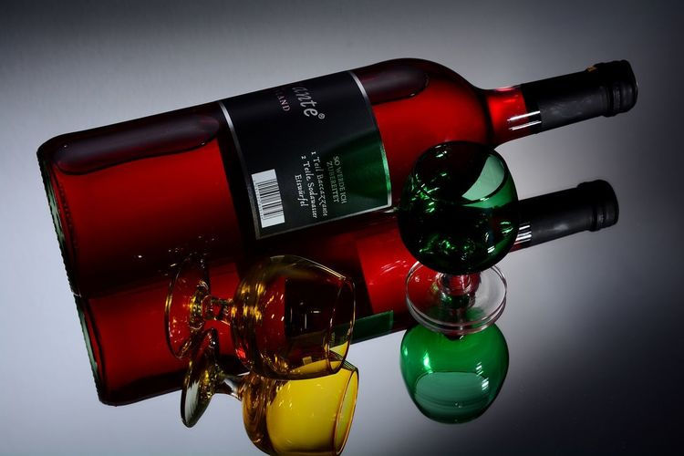 Close-up of red wine bottles against white background