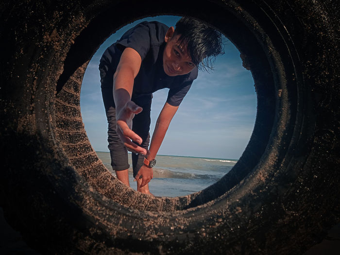 Young man gesturing while looking through tire against sky