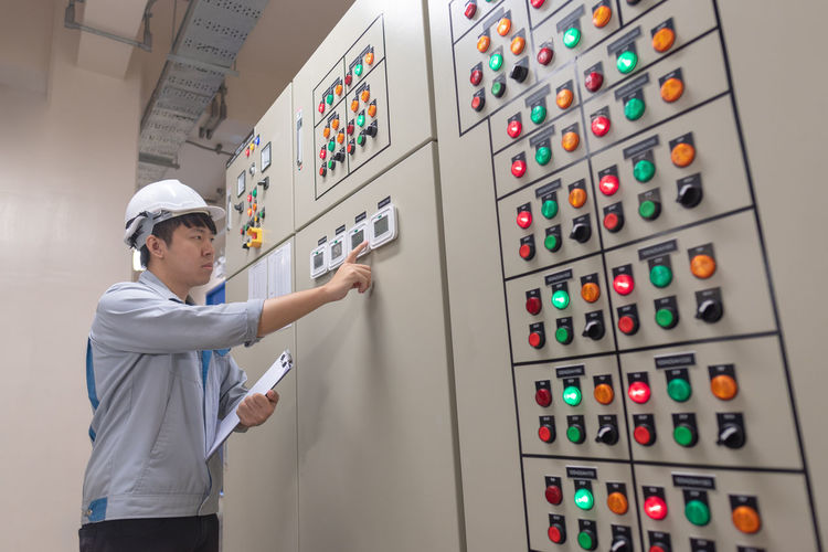 Control Panel Control Men Working Technology Indoors  One Person Occupation Standing Adult Protection Expertise Industry Security Examining Control Room Safety Holding Responsibility Push Button Complexity Quality Control