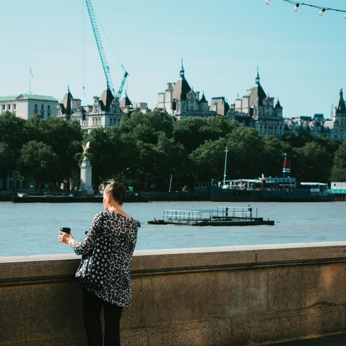 Woman standing by river in city against sky