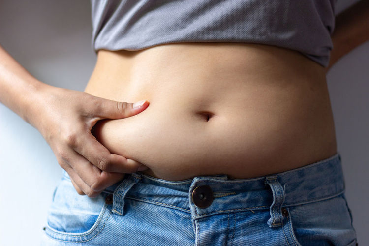 woman with overweight abdomen. hand holding excessive fat belly ,front view Abdominal Muscle Adult Anticipation Body Part Casual Clothing Close-up Dieting Females Front View Gray Background Healthy Lifestyle Human Abdomen Human Body Part Indoors  Jeans Lifestyles Midsection One Person Pregnant Studio Shot Women
