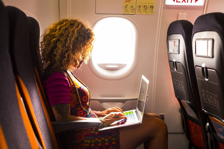 Woman using laptop while sitting in airplane