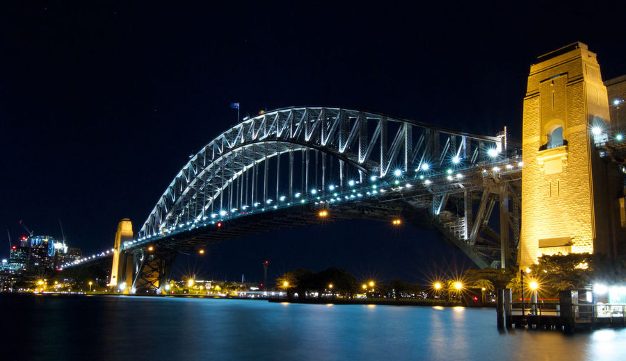 Illuminated Sydney Harbour Bridge Over Bay Of Water In City At Night