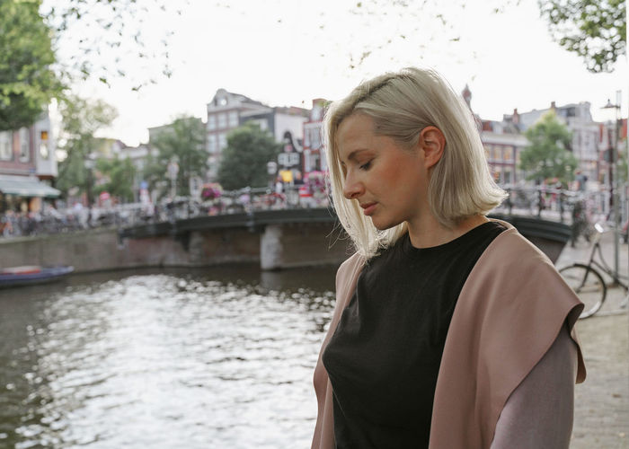 Young woman looking at canal in city