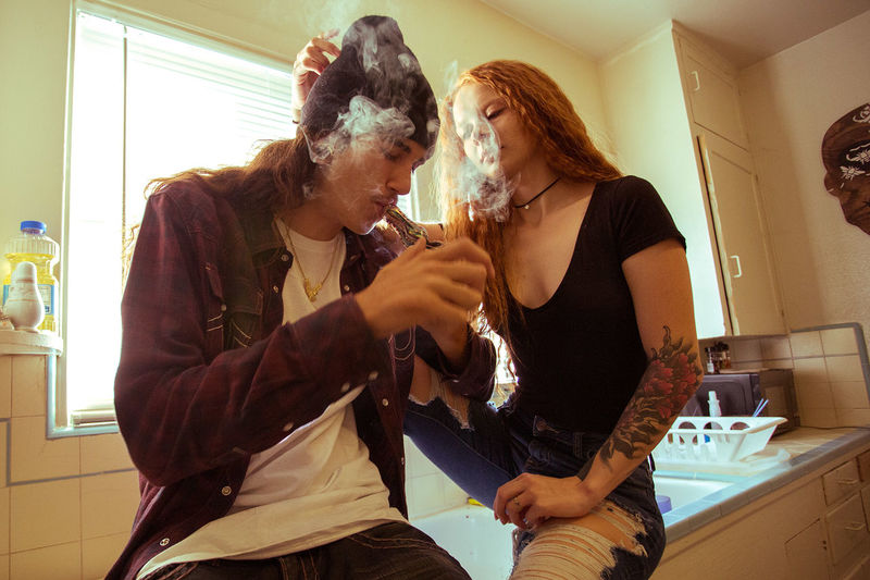 Young couple smoking in kitchen