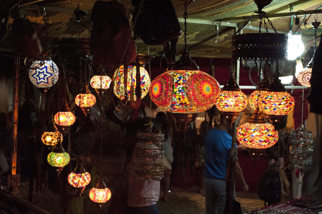 real people, for sale, hanging, market, illuminated, men, women, lantern, choice, variation, retail, standing, large group of objects, outdoors, lifestyles, two people, night, multi colored, people