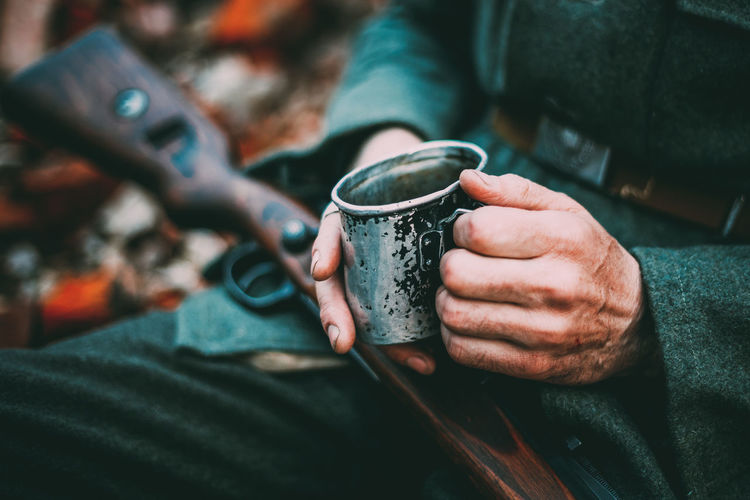 Unidentified Re-enactor Dressed As German Wehrmacht Infantry Soldier In World War II Holding Cup With Hot Water Or Tea In Camping In Autumn Forest. Weapon Gun Ww2 WWII Ww1 War Soviet Soldier Ussr Army Millitary Re-enactor German World Water Wehrmacht Tea Cup