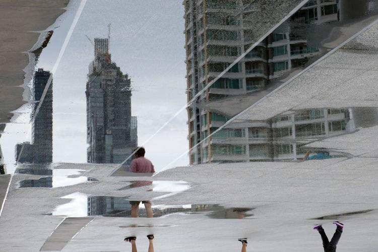 People walking by modern buildings in city